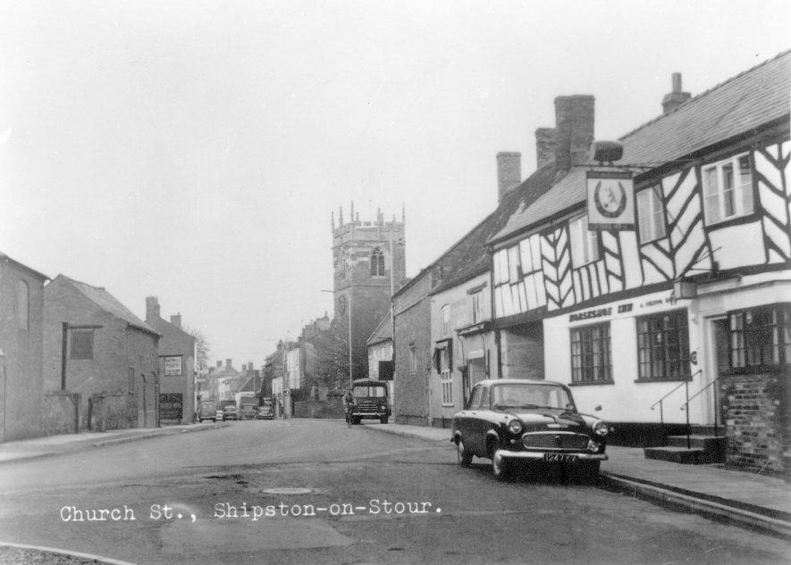 Looking along Church Street, with St Edmund's church in the background and The Horseshoe Inn on the right. Shipston on Stour.  1950s |  IMAGE LOCATION: (Warwickshire County Record Office)