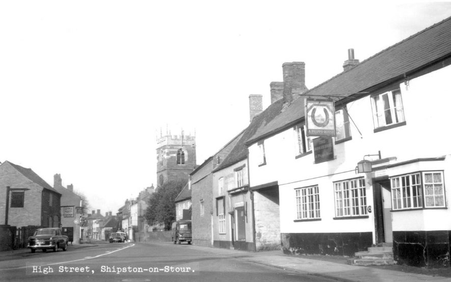 View looking along Church Street (not High Street as shown on the photograph), Shipston on Stour. The Horseshoe Inn is seen on the right and it is interesting to note the change of facade from that in other pictures taken a short time before.  1960s |  IMAGE LOCATION: (Warwickshire County Record Office)