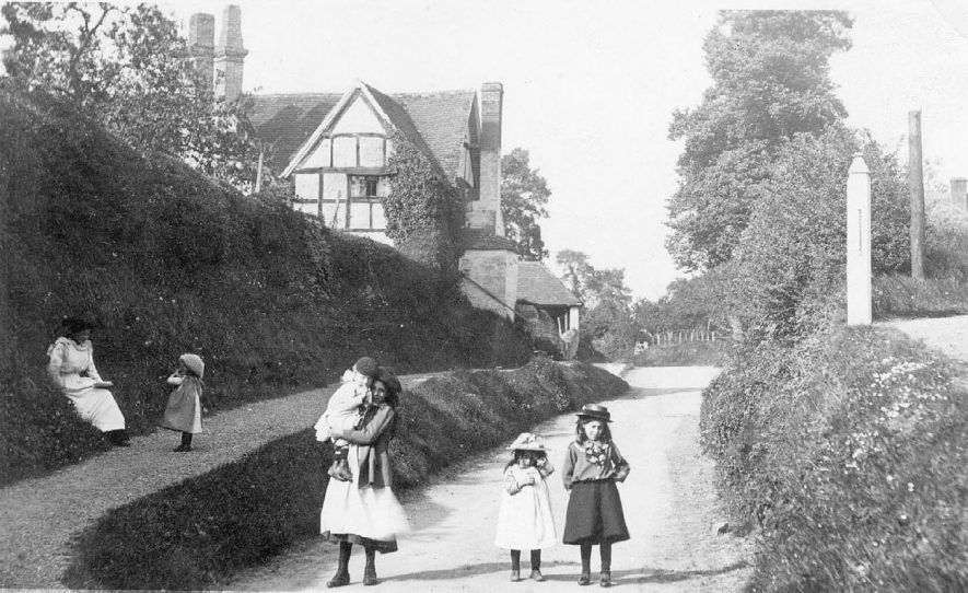 Street showing large timbered house, Exhall, nr. Alcester. Children, mixed ages, with adult 1900s |  IMAGE LOCATION: (Warwickshire County Record Office)