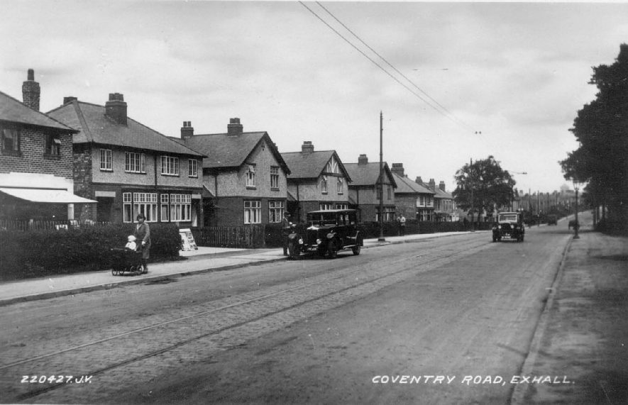 Coventry road, Exhall, nr Coventry. Semi-detached houses, motor cars.  1930s newsagent's shop (?) with awning, woman  with child in perambulator. 1930s. |  IMAGE LOCATION: (Warwickshire County Record Office)
