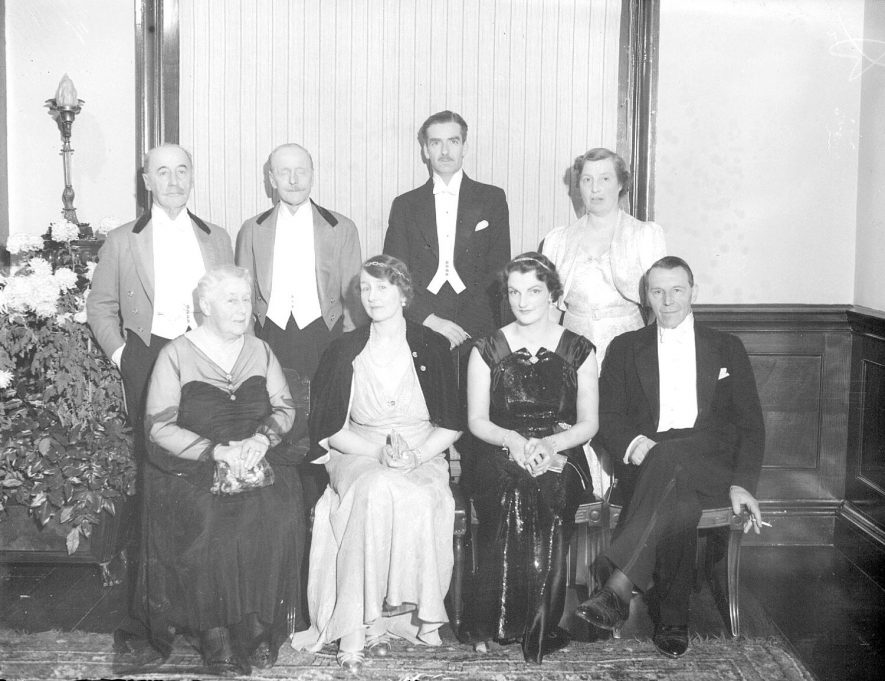 Group portrait taken at Ragley Hall at a ? Courier ball. Standing from the left - General Wiggin, Lord Henry Seymour, Anthony Eden and unknown person. Seated - Mrs Melville, Lady Helen Seymour, Spencer Flower and Mr Eden.  December 3rd 1937