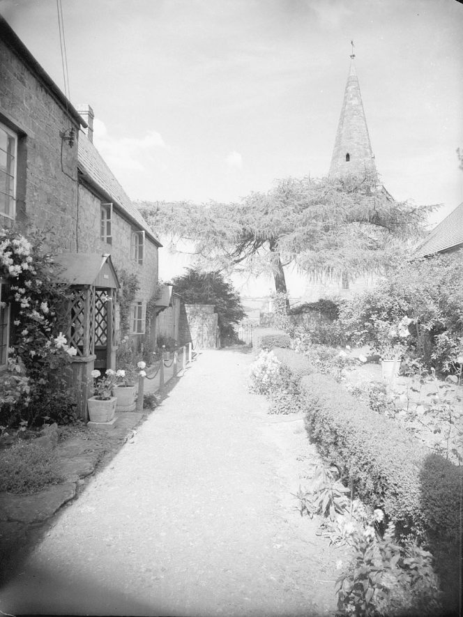 Row of cottages and gardens, with the church spire in the background, Shotteswell.  June 12th 1957 |  IMAGE LOCATION: (Warwickshire County Record Office)