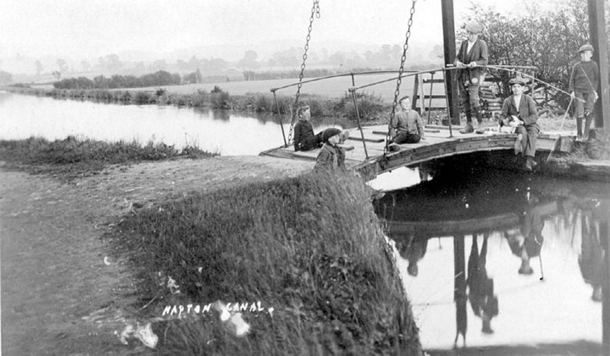 Canal at Napton, showing liftbridge. Boys fishing off the bridge, one has a dog/rabbit?  1910s [The lad has a dog - its not likely to be a rabbit!] |  IMAGE LOCATION: (Warwickshire County Record Office)