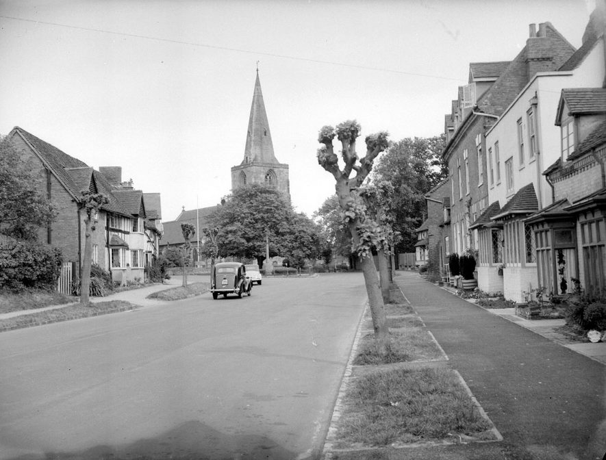 Street with cottages, looking towards parish church.  Two parked cars.  Tanworth in Arden.  1957 |  IMAGE LOCATION: (Warwickshire County Record Office)
