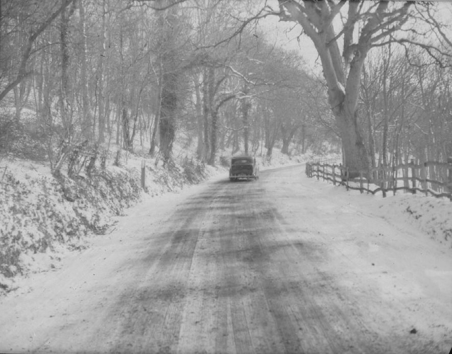 Exhall nr. Alcester. Country road under snow. Motor car.  1930s |  IMAGE LOCATION: (Warwickshire County Record Office)