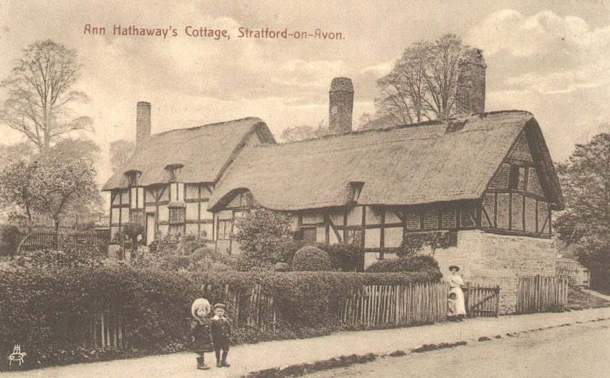 Ann Hathaway's cottage, Shottery, with a lady and child in the gateway and two children standing on the pavement.  1900s |  IMAGE LOCATION: (Warwickshire County Record Office)