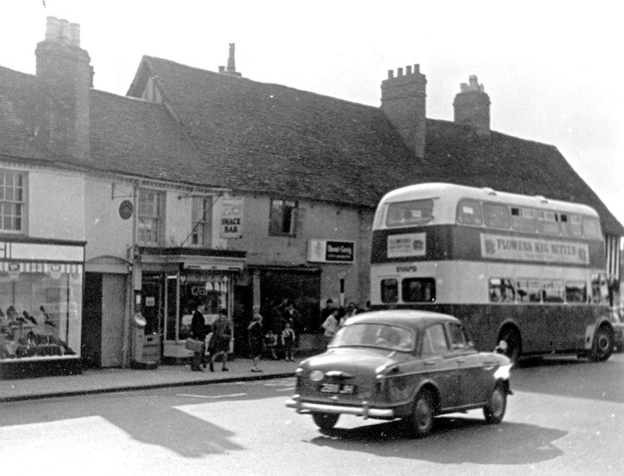 Wood Street, showing old shops, car and 'bus, Stratford upon Avon.  c.1961 |  IMAGE LOCATION: (Warwickshire County Record Office) IMAGE DATE: (c.1961)