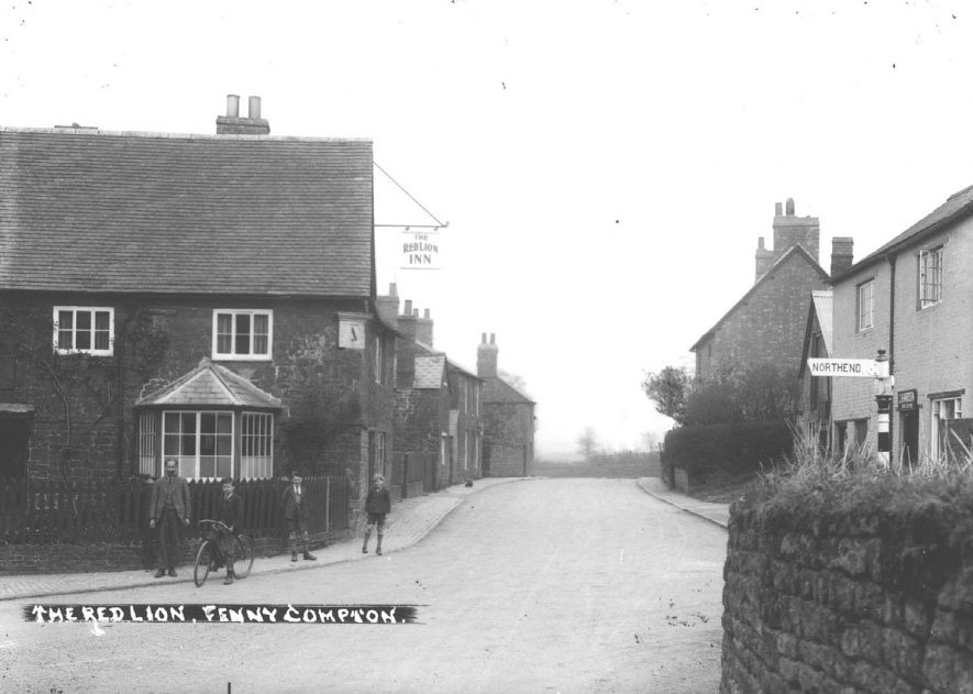 Part of Fenny Compton village with Red Lion Inn and signpost to Northend. Boys with bicycle.  1930s |  IMAGE LOCATION: (Warwickshire County Record Office)