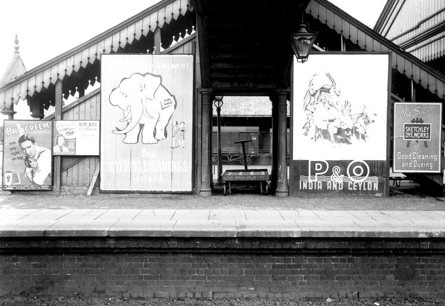 The railway station and advertising billboards, Stratford upon Avon.  1954 |  IMAGE LOCATION: (Warwickshire County Record Office)