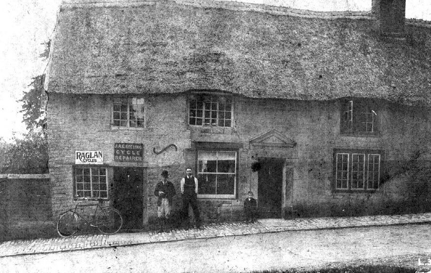 Abbey Green cottages; shows premises of J.A.G. Keeling, Cycle Repairer, with a bicycle and two men and a boy standing outside.  c. 1910 |  IMAGE LOCATION: (Warwickshire County Record Office)