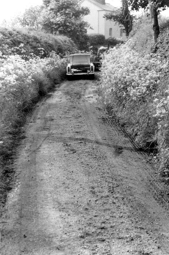 A car driving along Parsonfield, a country lane near Wootton Wawen. 1966. |  IMAGE LOCATION: (Warwickshire County Record Office)
