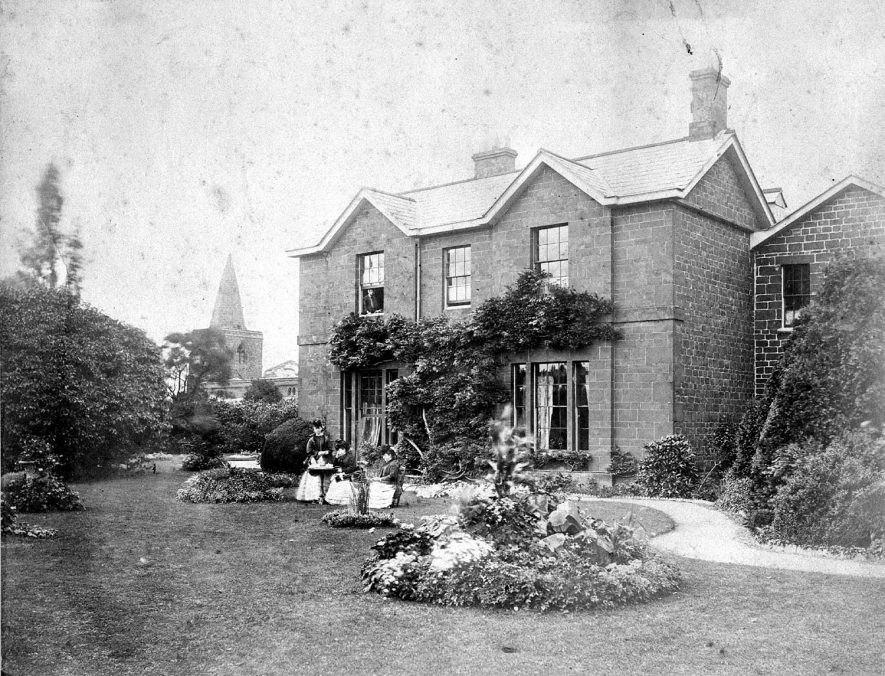 Stone built house ( vicarage?) and garden with flowerbeds and lawn in Fenny Compton. Three ladies at small tea table. Church seen at rear of house.  1890s    IMAGE LOCATION: (Warwickshire County Record Office)