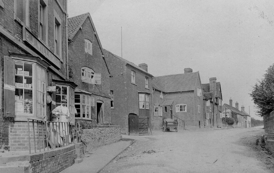 Street with cottages and general store (E.J. Wills) Double door leading through archway in building, Fillongley. Shopkeeper. Horse and cart.  1900s |  IMAGE LOCATION: (Warwickshire County Record Office)