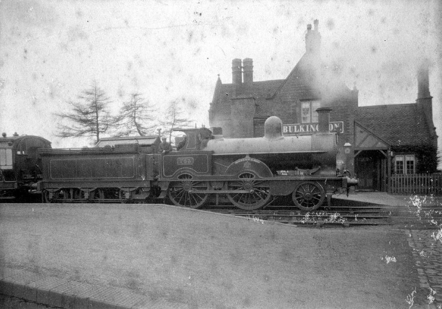 Bulkington. The railway station with steam engine and tender (L.N.W.R. 2-4-0 Samson and Waterloo class, built late 1880s onwards) Part of railway carriage. Station platform and building.  1910s    IMAGE LOCATION: (Warwickshire County Record Office)