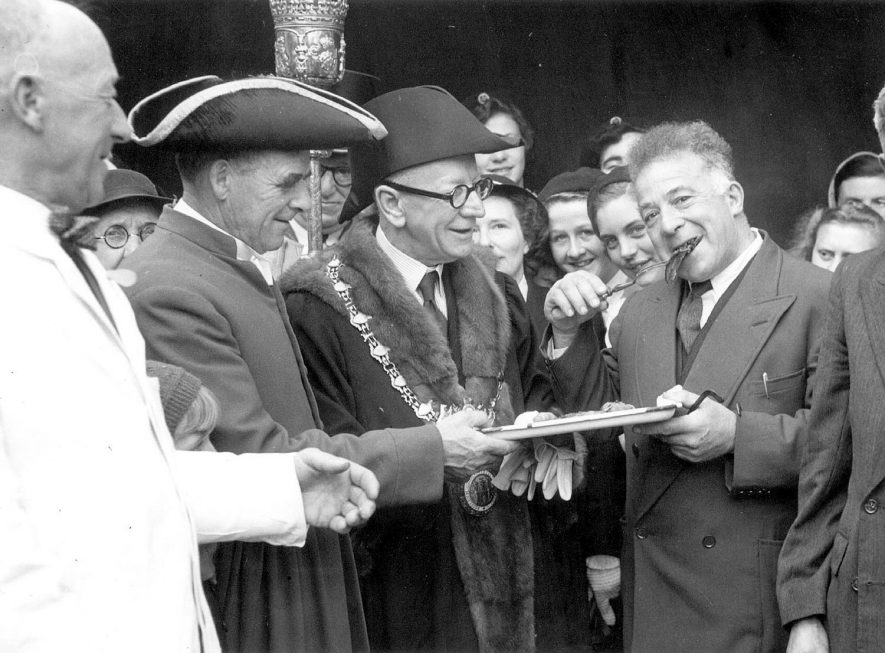 The mayoral party tasting the first slice of the pig roast at the Mop fair, Warwick. 1950s. A man with chain is handed a oplate by a smiling man with curly hair. |  IMAGE LOCATION: (Warwickshire County Record Office)