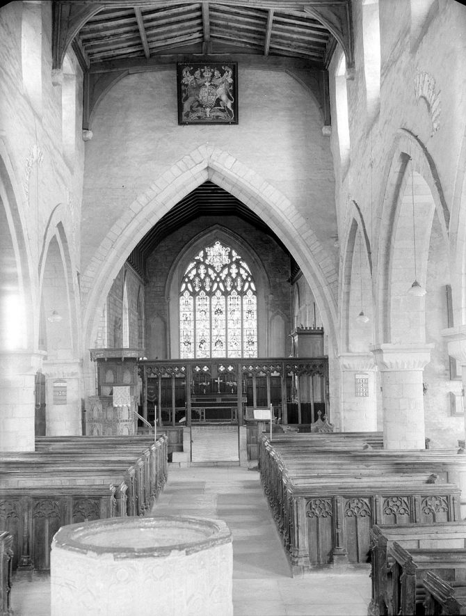 Tredington Parish Church interior with coat of arms over chancel arch, looking east.   1954. |  IMAGE LOCATION: (Warwickshire County Record Office)