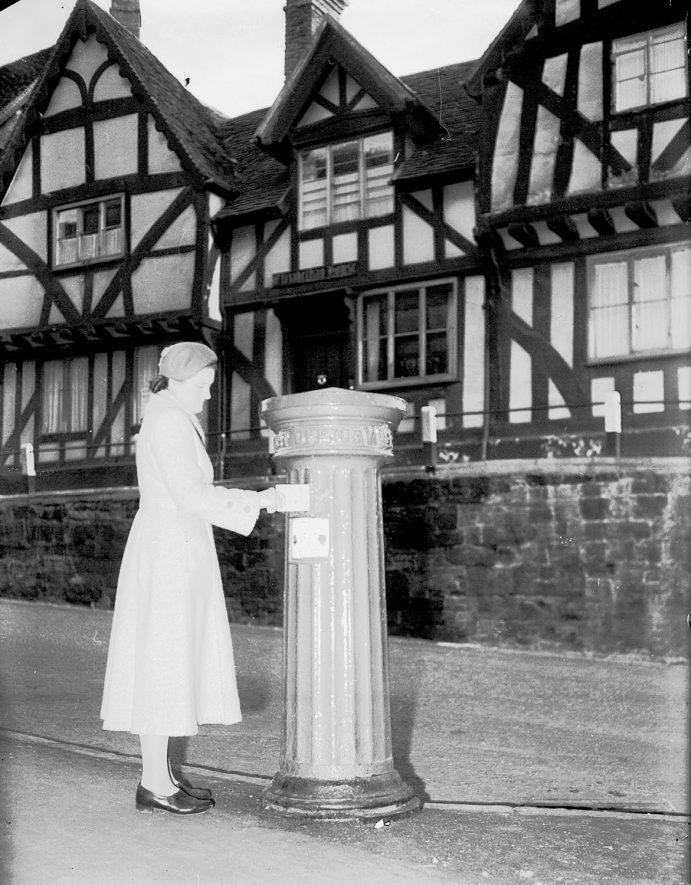 Woman posting letter in Victorian pillar box in High Street at Westgate  Tudor house in background.  Warwick.  1955.    IMAGE LOCATION: (Warwickshire County Record Office)