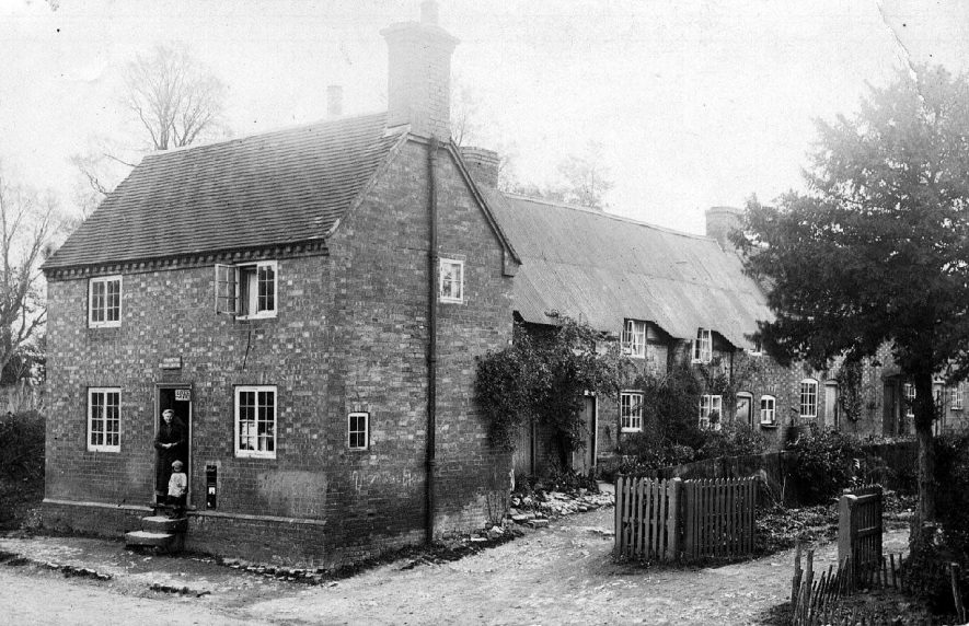 Frankton Post Office and row of cottages roofed with corrugated iron. Woman and child in doorway.  1900s |  IMAGE LOCATION: (Warwickshire County Record Office)