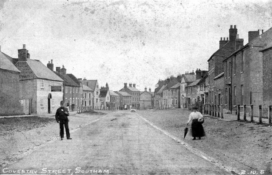 View looking south along Coventry Street, Bowling Green Inn on the left; policeman and lady with basket in  the foreground.  1900s    IMAGE LOCATION: (Warwickshire County Record Office)