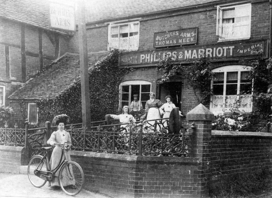 The Butcher's Arms public house, Fillongley.  Thomas Meek. Board advertising Phillips & Marriott ales and stout. Man in window. Woman and two girls on step. Woman with bicycle by gate.  1900s |  IMAGE LOCATION: (Warwickshire County Record Office)