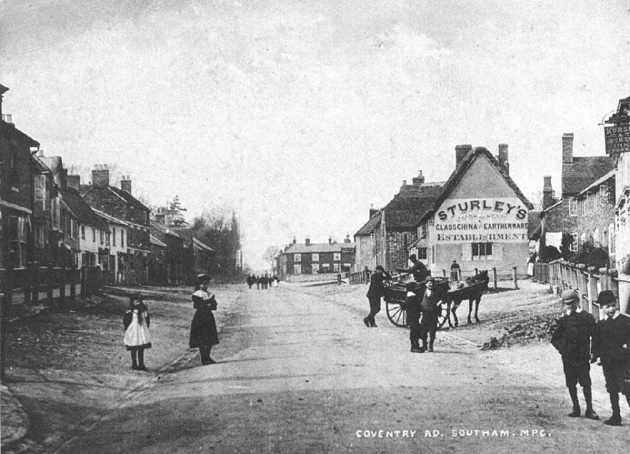 Looking north along Coventry Street; Sturley's glass, china and earthenware establishment, and the Horse and Jockey Inn on the right; people and a horse and cart standing in the road.  c. 1905 |  IMAGE LOCATION: (Warwickshire County Record Office) IMAGE DATE: (c.1905)