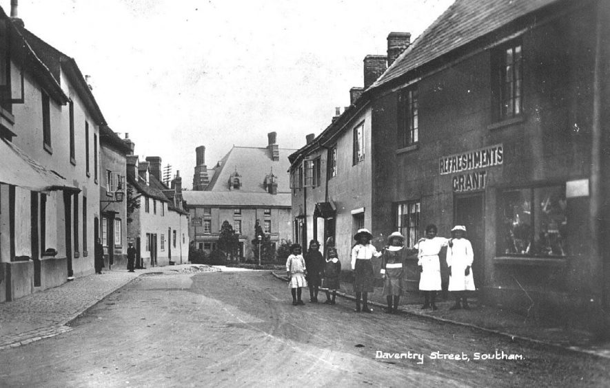 Daventry Street, looking west towards the convent and Crown Inn; shows shop selling 'Refreshments' owned by Grant, children lined up outside.  1910s