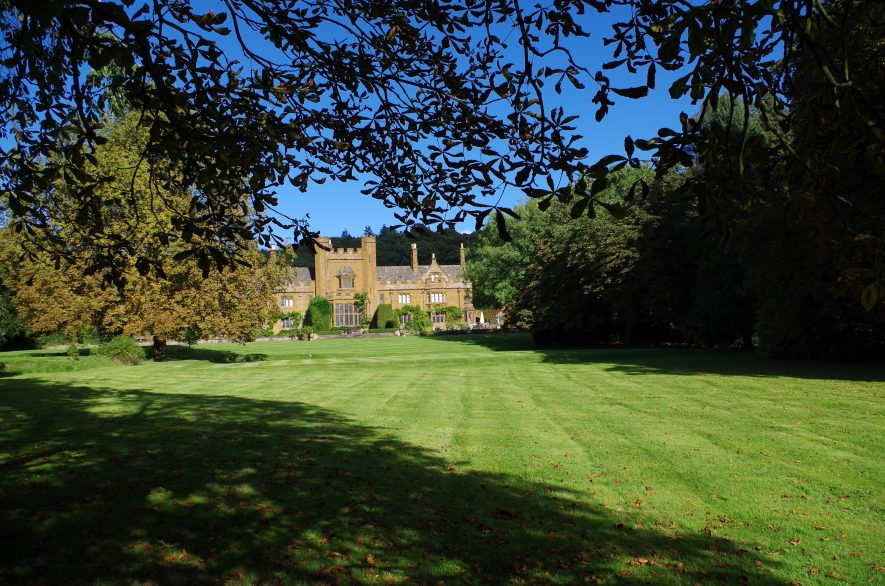 Avon Carrow from the front lawn. It is a sunny day, a stately home is in the background, and a tree on the left casts a shadow across the lawn.