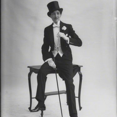 Portrait of Gwen Lally, the producer of the Warwick Pageant, by Bassano Ltd, circa 1913. This was a few years before they performed as a male impersonator in Stratford-upon-Avon. The subject is wearing a top hat and has inked on their face a pencil thin moustache. They are sat on the edge of a table. | Image originally from the National Portrait Gallery, London