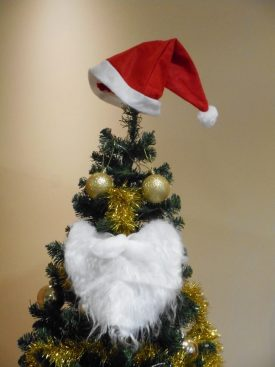 The Warwickshire County Record Office Christmas tree appears to have developed a personality. A beard is draped over the tree, a santa hat is on the top, and two baubles take the place of eyes, along with tinsel for a nose. | Image courtesy of Becky Hemsley