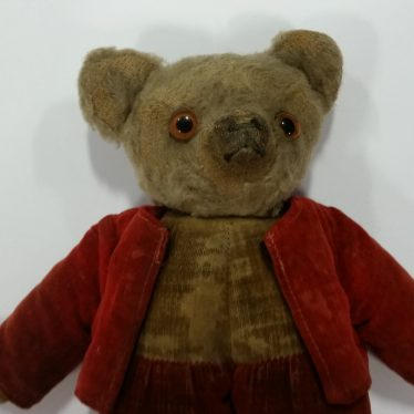 A Teddy Bear dating from the 1920s. The bear is brown, and dressed in a red 'waistcoat' of sorts. | Image courtesy of Warwickshire Museum