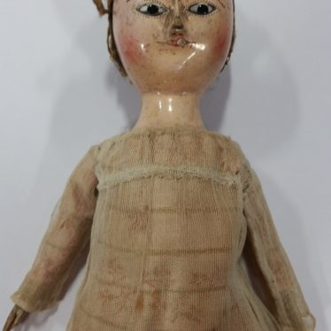 A wooden doll from c. 1810. The doll is wearing a beige dress with a patt6ern in a pink. The head has the hair tied back sharply, and the doll has blue eyes with what looks like rouge applied to the cheeks. | Image courtesy of Warwickshire Museum