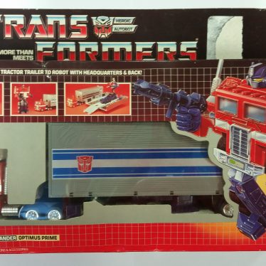 Transformers. Optimus Prime from 1984. A robot is marked on the box on the left, holding a gun and 'dressed' in red. The window for the box shows it contains a truck. | Image courtesy of Warwickshire Museum