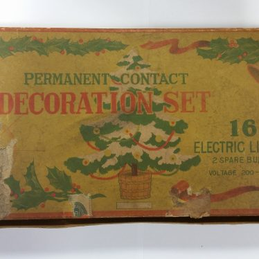 Christmas tree lights from the 1930s. The box is yellow with a picture of a christmas tree in the middle. The box says 'permanent contact decoration set. 16 electric lights.' | Image courtesy of Warwickshire Museum
