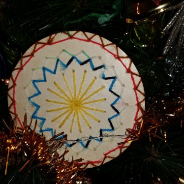 Handmade decoration made by the author and her mum, c. 1978. The central feature is a white disc with various shapes decorated within. | Image courtesy of Warwickshire Museum