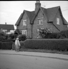 Cottages, 200 years old, Hampton on the Hill, 1967. A lady walks past the semi-detached houses. | Warwickshire County Record Office reference PH212/25/1. Part of a photographic survey of Warwickshire parishes conducted by the Women's Institute.