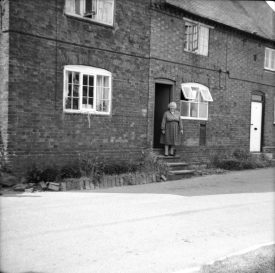 Post Office and Mrs King, Hampton on the Hill, 1967. Mrs King is standing outside the post office. | Warwickshire County Record Office reference PH212/25/7. Part of a photographic survey of Warwickshire parishes conducted by the Women's Institute.