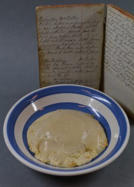 The batter pudding, and its recipe. The recipe stands behind a blue and white hooped bowl, which has the pudding (in off-white and slime) within. | Image courtesy of Robert Pitt, who did fine things with little material. Warwickshire County Record Office reference CR4817/1