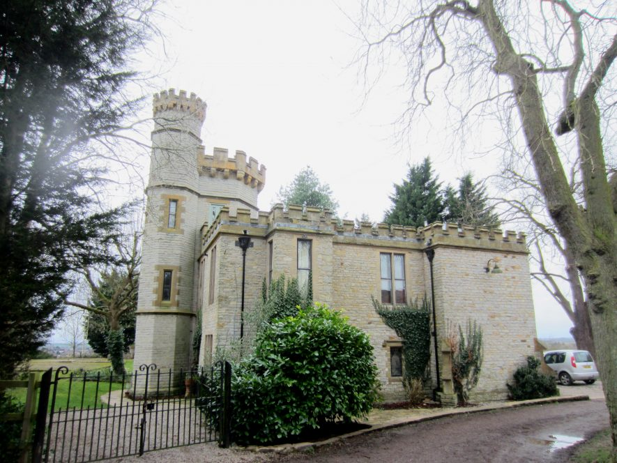 Two-storey stone building with crenellations and attached tower with slit windows and crenellations | Image courtesy of Anne Langley