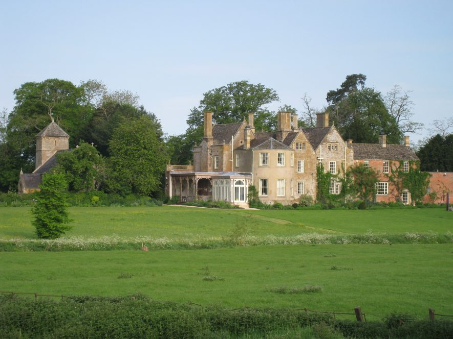 Tidmington House from the East. A large pale coloured building is seen across a green field / lawn. | Image courtesy of Chris Rice