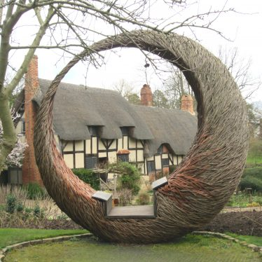 Anne Hathaway's Cottage and willow circle, 2017. Timber-framed 2-storey building with thatched roofframed by a willow circular seat | Image courtesy of Anne Langley