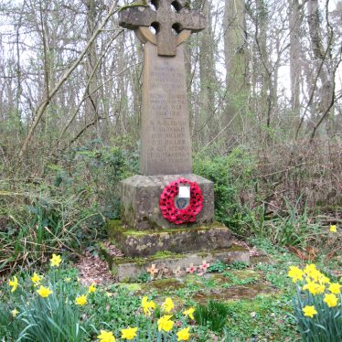 Stone memorial with cross and circle at the top and names carved on the shaft. Poppy wreath at the foot, small crosses planted in front of the memorial and daffodils flowering | Image courtesy of Anne Langley