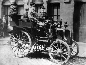 1899 Daimler, driven by Charles Crowden. Open car with 4 passengers on a cobbled urban street with bystanders | Image courtesy of Culture Coventry, photographer unknown.