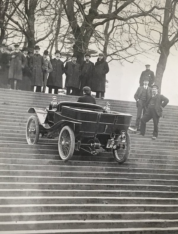 Lanchester car in 1903 promotional film. The car is driving up some steps, being watched by onlookers. | Image courtesy of the Lanchester Collection, Coventry University