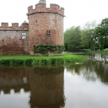 Wide moat around red sandstone crenellated castle wall and tower reflected in the water; trees beyond | Image courtesy of Anne Langley