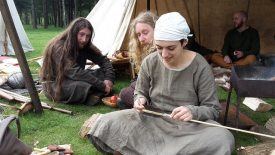 Warwickshire residents fletching arrows and relaxing at an Anglo-Saxon reenactment event. A woman wearing a headscarf wields a knife towards the end of a pole, looked on by two long haired bearded gentlemen, one of whom turns round to view. | Photograph courtesy of Cathy Hemsley