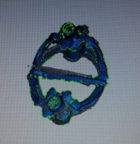 A 3D image of the Warwick medieval brooch. The shape is near circular, with a piece of metal bisecting. The colours of the scan are mostly blue, with green 'blips' at edges. | Image courtesy of Warwickshire Museum / Pangolin Digital