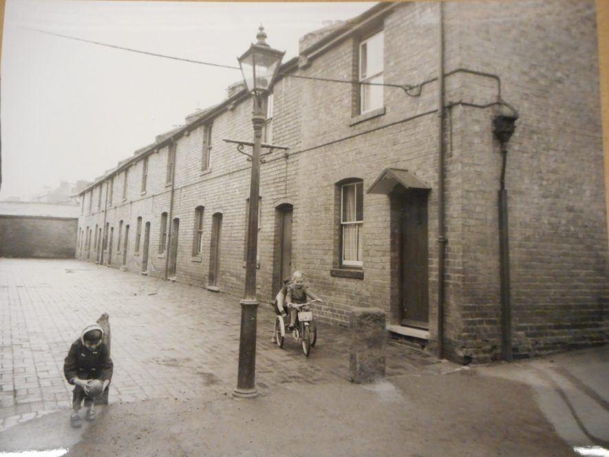 Union Walk, 1960s. Terraced houses with cobbles in front, a child on a bike is on the right, whilst on the left, a child appears to be holding a ball. | Warwickshire County Record Office reference PH659