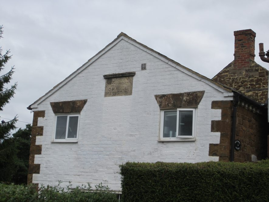Former Primitive Methodist Chapel, Northend, 2017, now called 'Old Chapel Cottage'. A regrettable red brick extension (visible in 2000) has now been removed and the brick front painted white. The side walls are made of local ironstone (maybe the front too originally?) with dentillated detail under the eaves and the roof is of slate. The plaque says 'PRIMITIVE METHODIST CHAPEL ERECTED 1855'. One storey building with sides of ironstone, front of brick painted white, with plaque and small windows | Image courtesy of Anne Langley