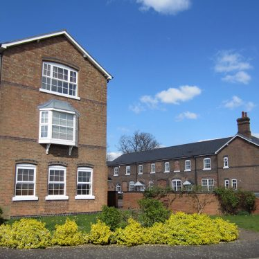 3-storey yellow brick building with blue engineering brick features and bow window added; most of courtyard 2-storey, red-brick with engineering brick details and slate roof. Shrubs in border and garden wall in foreground | Anne Langley