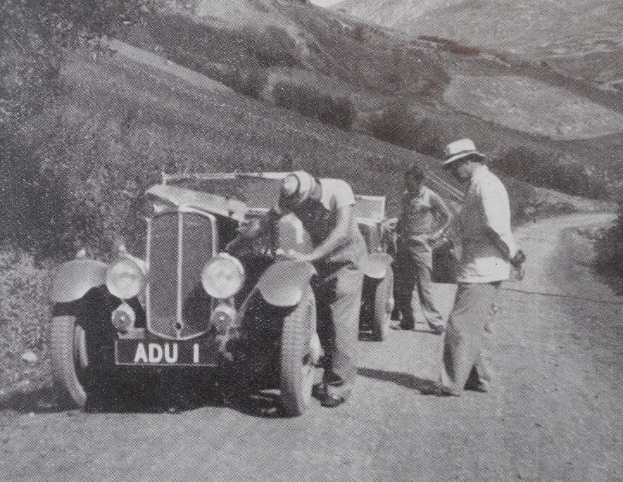 Donald Healey adjusts the carburettor on Leveretts car so as to give maximum performance at high altitudes. Originally published in the booklet 'Gloria In Exelsis', 1934. | Warwickshire County Record Office reference CR4804/4/4